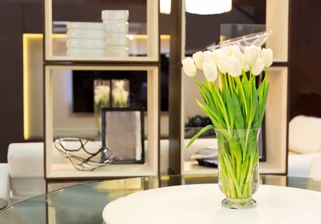 luxury apartment: Bouquet of white tulips stands on the table in the room
