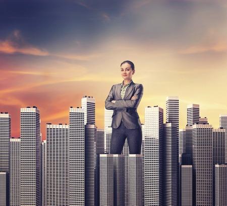 Lächelnde Geschäftsfrau, die unter den Bürohochhäusern, auf den Sonnenuntergang Standard-Bild - 45583954