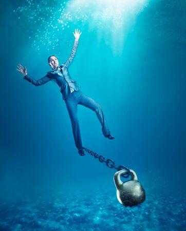 ahogarse: Empresaria con pesa en la mano que se hunde en el mar