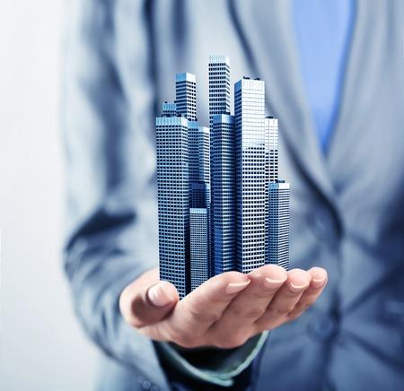 bienes raices: Edificios de oficinas de pie en la palma de la mano humana