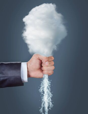 squeezing: Male hand squeezing a cloud over grey background