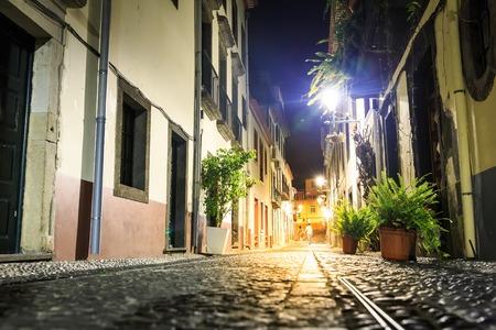 femme romantique: Couple marchant dans le bout de la rue européenne étroite tht soir, Portugal, Madère