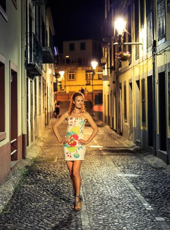 street night: Woman standing in the night street with hands on hips Stock Photo