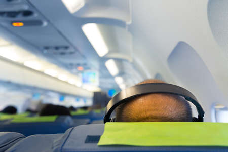 aeroplanes: Mans head in headphones in the plane salon close up