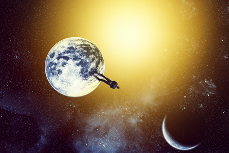 gravity: Businessman is standing on the planet in front of the sun Stock Photo