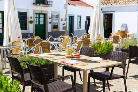 the place is outdoor: Restaurant outdoor with served table on the street, Portugal, Madeira Stock Photo