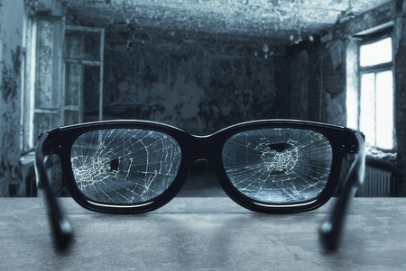 vision repair: Broken eyeglasses with cracks in an old room
