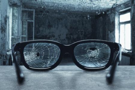 Gebroken bril met scheuren in een oude kamer Stockfoto