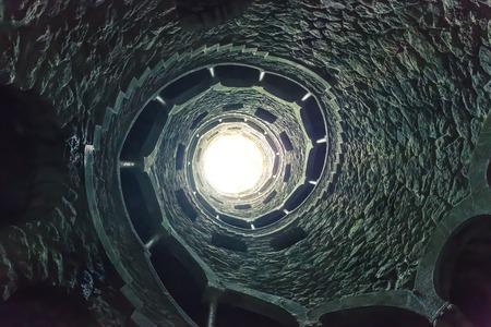 espiral: Luz al final de la escalera de caracol Foto de archivo