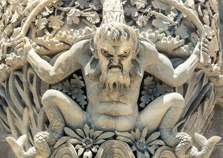 Stucco statue of male monster close up
