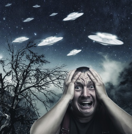 Erschrocken durch den Menschen UFO in der Nacht schreiend im Wald Standard-Bild - 45947241