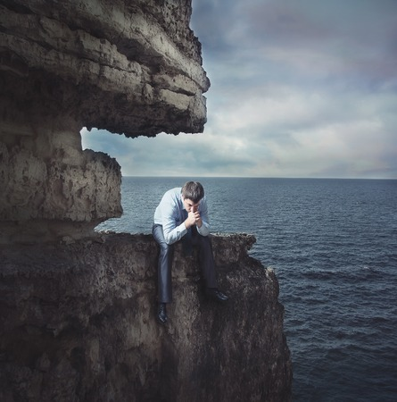 man sad: Frustrated businessman sits on edge of the cliff near the sea