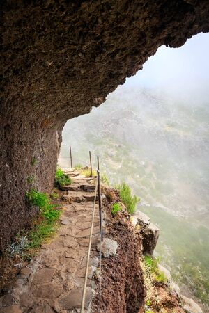 handrail: Mountains in clouds with path with handrail
