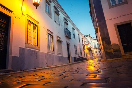paved: Narrow european street with paved road in the evening, buildings with balconies, Portugal