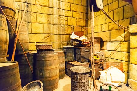 lumber room: Old lit lumber room with wooden baskets, barrels and ropes Stock Photo