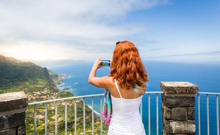 Young woman with red hair standing back takes photo of summer seaside landscape, Portugal, Madeira photo