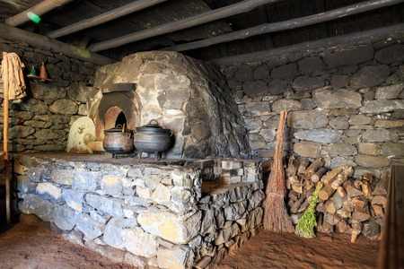 wood stove: Ancient kitchen interior with furnace, pots and lumber