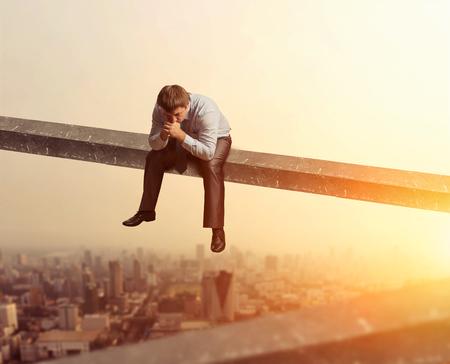 hombre solo: hombre de negocios pensativo se sienta en la tabla de madera encima de la ciudad