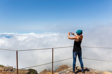 Young woman takes photo in cloudy mountains, Portugal, Madeira photo