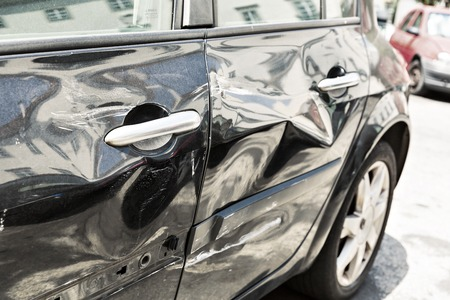 fender bender: Closeup of modern black car with dents Stock Photo