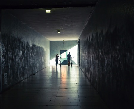 walkway: Young woman and man with bicycles in the tunnel underground Stock Photo