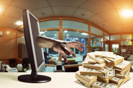 financial security: Hand coming out of a monitor and stealing money Stock Photo