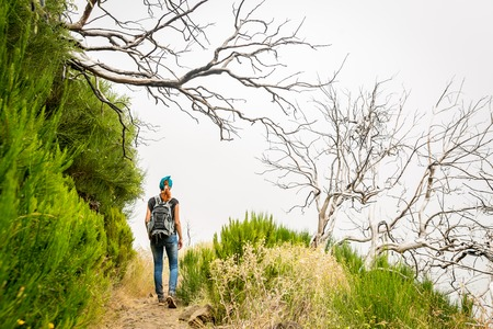 Woman hiking in obscure cloudy mountains, Portugal, Madeira photo