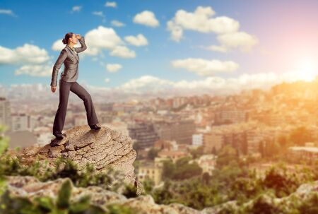 among: Confident businesswoman standing on the mountain looks at the city
