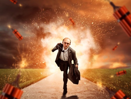 Businessman is running from dynamite exploding on the road