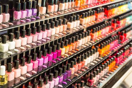 cosmeticos: Conjunto de diferentes esmaltes de uñas en los estantes en la tienda de cosméticos
