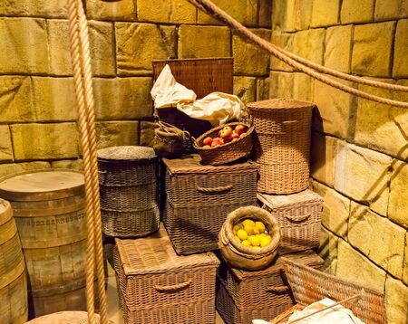 urban decline: Old lit lumber-room with wooden baskets, barrels and ropes