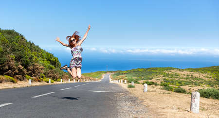 seaside: Young woman jumping on the road in mountains, Portugal, Madeira