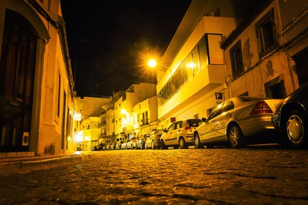 empedrado: Narrow european street with paved road and modern cars