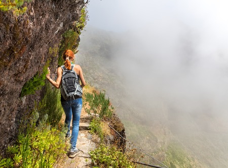 portugal: Young woman walking in the path on the mountain edge, Portugal, Madeira Stock Photo