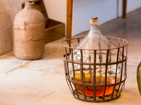 bootle: Carboy with some beverage stands on the floor in the kitchen