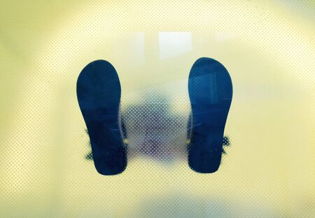 vestige: Bottom view through the glass of mans shoes feet