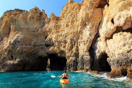 Man kayaking in the rocky tunnel in the sea, Portugal Stock Photo