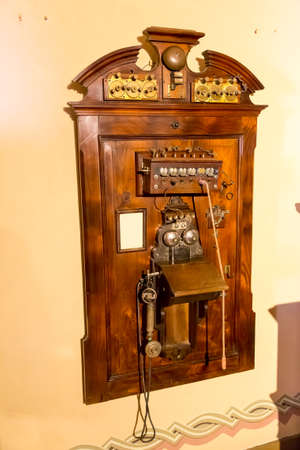 antique telephone: Wooden antique telephone on the wall Stock Photo