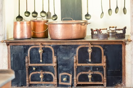 Retro kitchen interior with old pans, pot on the furnace Foto de archivo