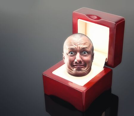 fancy box: Male astonishad face in red jewelry box over grey Stock Photo