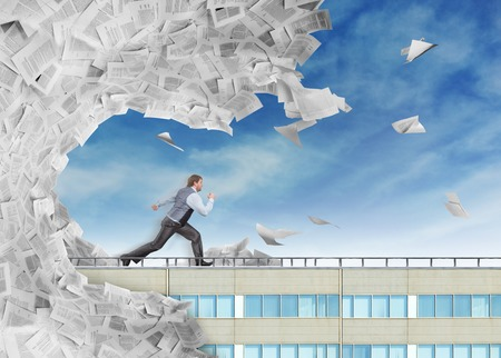 Businessman is running from big wave of paperwork