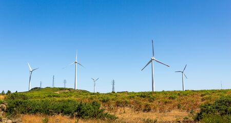 mill valley: Windmills in the green valley against blue sky Stock Photo