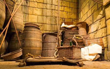 millstone: Old lit lumber-room with wooden baskets, barrels and ropes