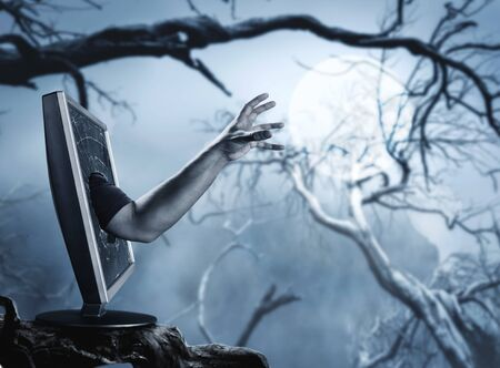 horrific: Male hand rising from computer screen in the horrific forest Stock Photo