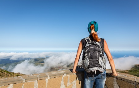 knapsack: Young woman standing back with a backpackon the peak