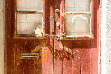 faded: Old wooden faded door locked with chain close up