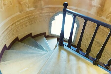 Spiral stairs with a little round window Stock Photo