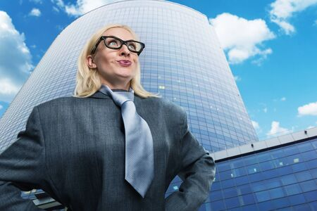 self assurance: Surprised geek businesswoman near the skyscraper