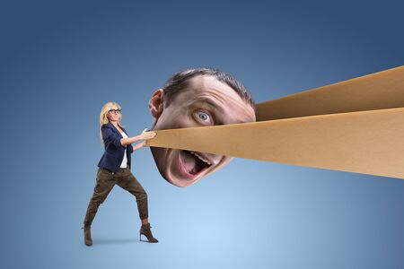 psych: Woman pulling mans head in a slingshot Stock Photo
