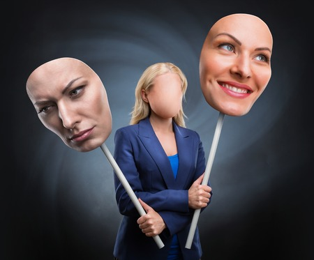 mood: Businesswoman choosing face over grey background Stock Photo